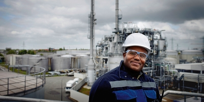 Close up picture of an engineer in front of a refinery